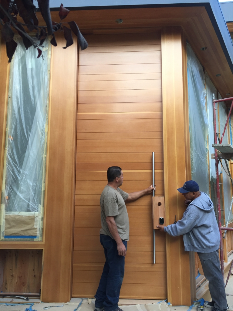 Large, wood front door with pivot function
